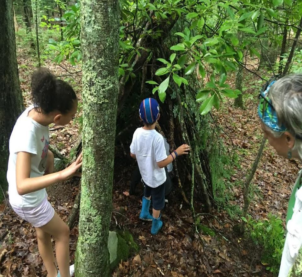 Two children are building an outdoor shelter